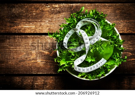 Salad with fitness  measuring tape over wooden background.  Diet Food and healthy lifestyle concept. - stock photo