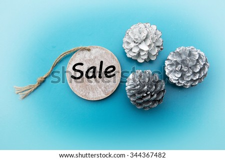 'Sale' written on wooden tag with white pinecones on blue background