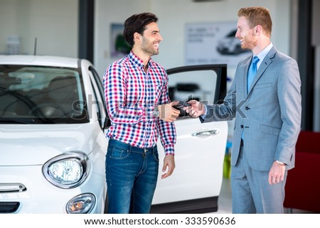 Sales situation in a car dealership, the dealer giving key of car at young male, - stock photo