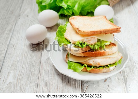 sandwich with chicken breast , egg, lettuce, cheese and mayonnaise on a wooden background
