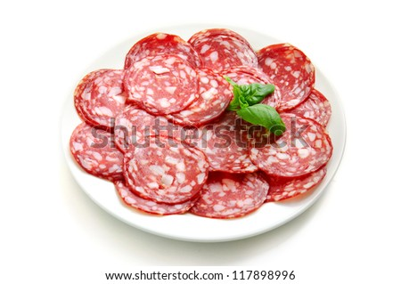 Sausage slices with basil leaf on the dish isolated - stock photo