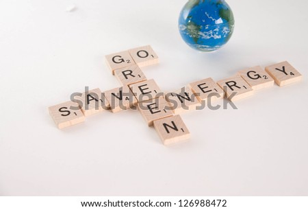 """Save Energy, Go Green"" concept spelled in Scrabble letters with out of focus world globe in the background. Isolated on white background"
