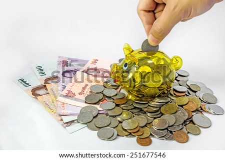 Saving, Coin with hand putting a coin into piggy bank - stock photo