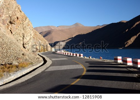 Scenic road beside Yamdrok Tso Lake, one of the three largest lakes of Tibet. Tibet - stock photo