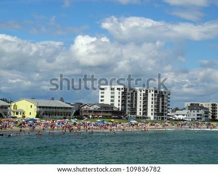 Scenic view of Old Orchard Beach in Maine from the end of the pier, several hundred feet out over the ocean, on a sparkling, sunny summer day. - stock photo