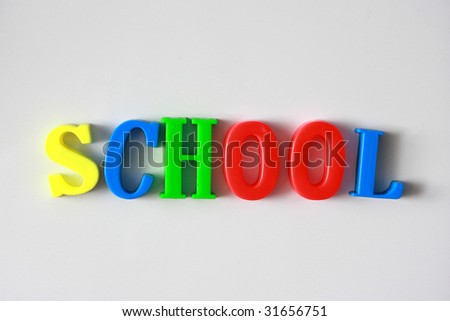 """School"" text, made from plastic letters on white magnetic board"