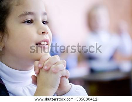 Schoolgirl  fingers clasped in prayer in the classroom - stock photo