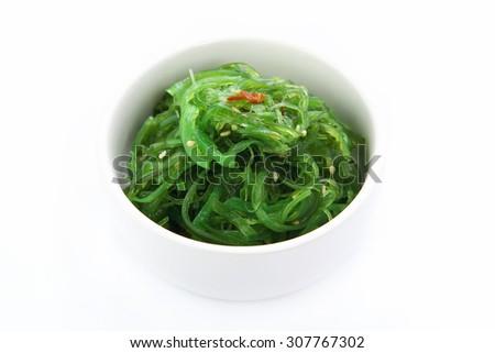 Seaweed Salad in white bowl on white background - stock photo