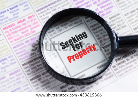 """Seeking For Property"" red and black text on blurry image of newspaper with magnifying glass on it symbolic as search"