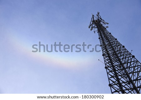200' Self support tower (lattice tower) and the rainbow. Tower climber reaching the top to inspect the wireless antennas. - stock photo