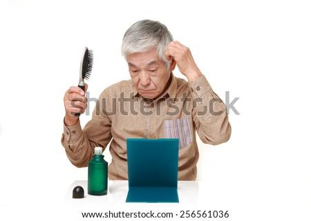 senior Japanese man using hair restorer - stock photo