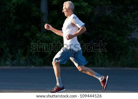 senior man running in the summer park - stock photo