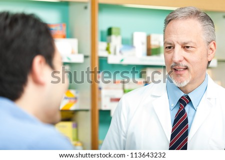 Senior pharmacist dealing with a customer - stock photo