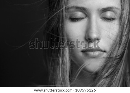 Sensual woman model with windswept flying hair on dark background