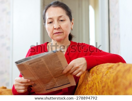serious mature woman looks newspaper at home - stock photo
