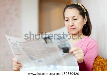 serious woman reading newspaper at home - stock photo