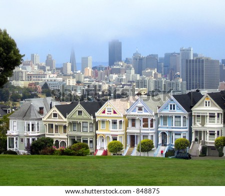 """Seven Sisters"" victorian homes with fog enshrouded San Francisco as a backdrop"