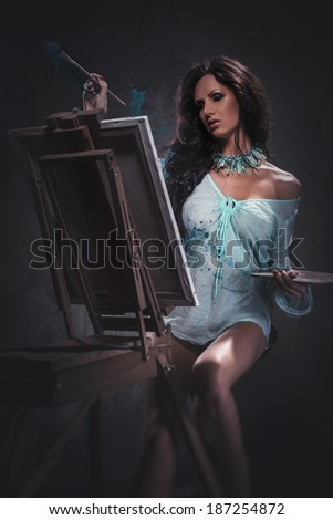 Sexy woman painting, studio shot - stock photo