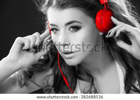 Sexy young woman dancing listening to music in headphones - stock photo