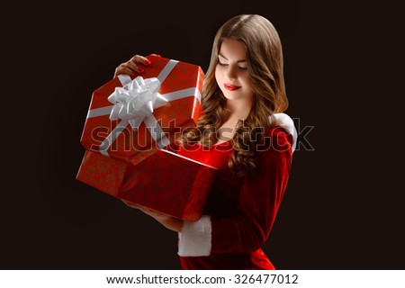 sexy young woman in red suit of Santa Claus  with gifts. On a dark background.