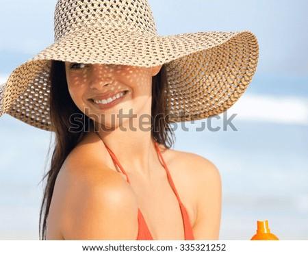 sexy young woman on the beach applying sun cream - stock photo