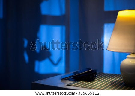 shadow of a burglar or thief sneaking to backdoor at night, view from inside the residence. - stock photo