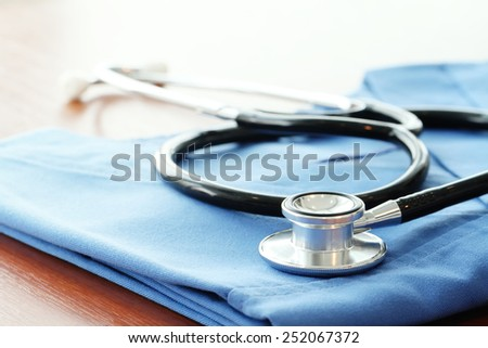 shallow DOF of Stethoscope with blue doctor coat on wooden table and  background  - stock photo