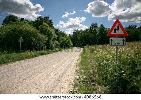 """Sharp turn"" sign by the road - stock photo"