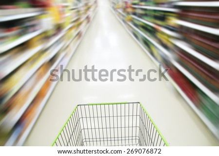 Shopping in supermarket. blurred shopping cart ,Closeup detail of a woman shopping in a supermarket - stock photo