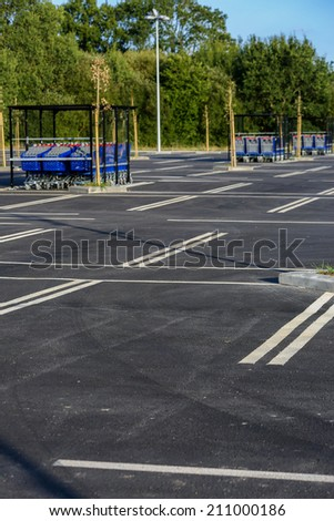 shopping trolleys on empty supermarket parking - stock photo