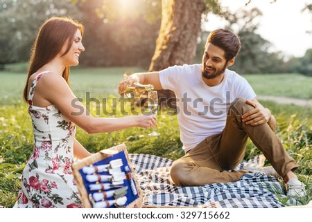Shot of a young couple drinking champagne and enjoying a picnic outdoors. Selective focus. - stock photo
