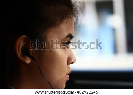 Silhouette edge Asian girl sitting in the  car listening to music from smartphone in-Thailand