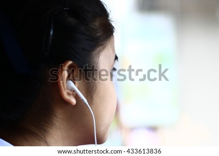 Silhouette edge Asian girl sitting in the car listening to music from smartphone in-Thailand.