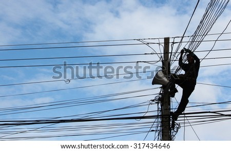 Silhouette Electrician Man on electric poles. Electrical repairs are made to restore them to normal  ( Silhouette style ) - stock photo