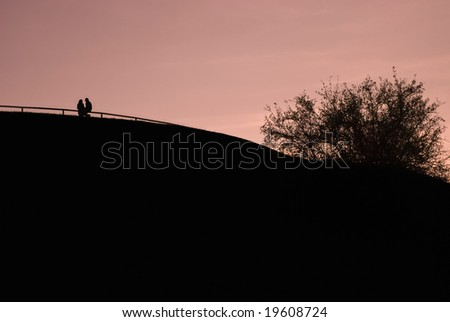Silhouette of a Couple on a Hill - stock photo