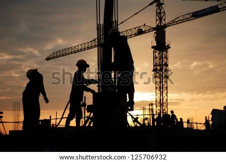 silhouette of construction worker on construction site - stock photo