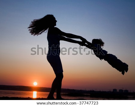Silhouette of mother which turns the child against a sunset and water - stock photo