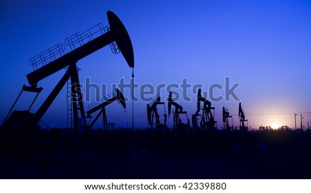 Silhouette of oil well - stock photo