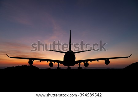 Silhouette of  passenger aircraft, airline on beautiful sunset background - stock photo