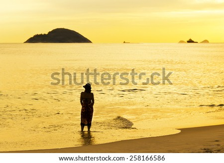 Silhouette of woman - Sunset in day 40 - sea and sky yellow - Rio de Janeiro - stock photo