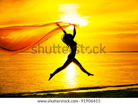 Silhouette of young girl, jumping with silk cloth against of sea sunset - stock photo