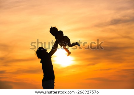 silhouettes of father and little daughter playing at sunset