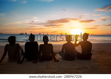 silhouettes of  group of children on beach at sunset - stock photo