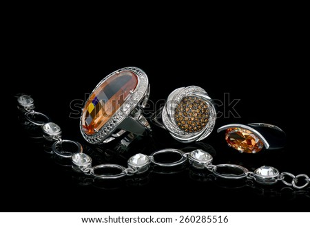 3 Silver Ring with Front with a bracelet, silver on black background. - stock photo