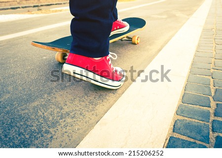 skateboarder trick in beach road - stock photo