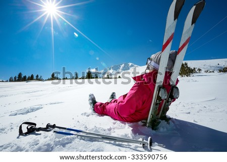 Skier relaxing at sunny day on winter season with blue sky in background - stock photo