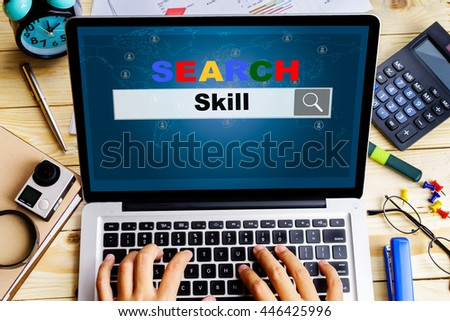 """""""Skill"""" words on laptop screen with a man try to search it on wooden table with camera, clock, calculator, diary and pen - search, job, requirement and finding concept - stock photo"""