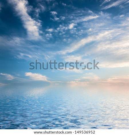 Sky with clouds reflected in water surface.  - stock photo