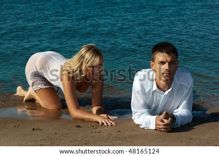 slavonic couple - blonde girl in peignoir and brown haired man in white shirt taking their time on the beach. girl is playful, man is serious