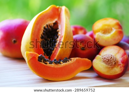 sliced papaya and mangoes fruits on the table. - stock photo